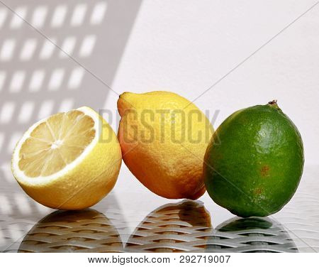 Still Life With Two Ripe Juicy Lemons And Green Lime Against A High Key Background With Space For Yo
