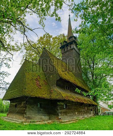 Gothic two-tier wooden Church of the St. Archangel Michael of 17th century with tower among the age-old trees in village Krainykovo, Zakarpattia Oblast, Ukraine poster