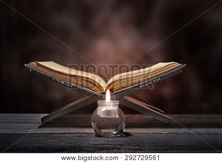 Quran Open In Wooden Placemat And Candle On Wooden Table Over Blurry Background