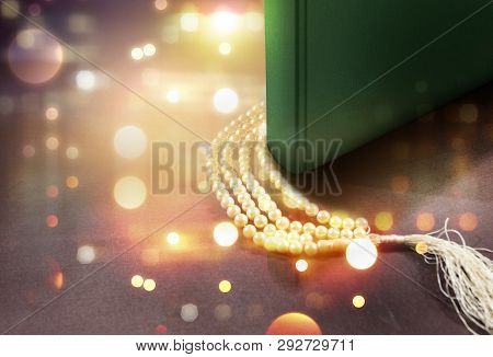 Quran And Prayer Beads On The Table With Blurry Lights Background