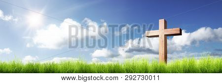 Christian Cross On The Green Grass With Sunlight Over Blue Sky Background