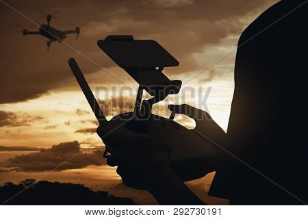 Silhouette Rear View Of Man Controlling Drone Which Flying In The Air With Sunset View Background