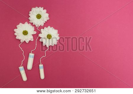 Three Flowers From Hygienic Tampons On A Pink Background.