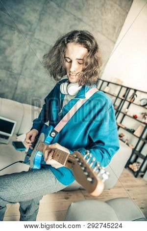 Careless Long-haired Man Being Inspired While Playing Music