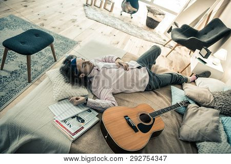 Careless Dark-haired Male Musician Resting In Bedroom After Repetition