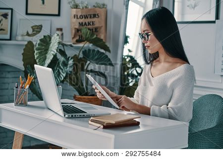 Working Hard. Beautiful Young Woman Working Using Digital Tablet While Sitting In Home Office