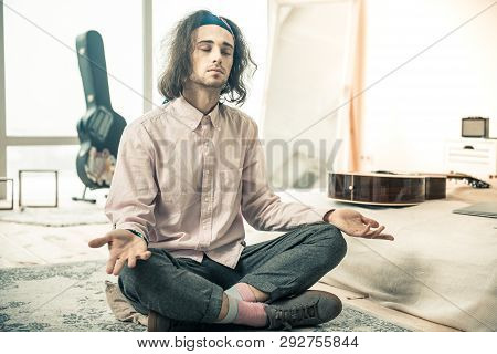 Tranquil Good-looking Young Guy Having Meditative Period