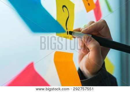 Businesswoman Writing Question Marks On Colorful Sticky Note Paper On Office Whiteboard, Selective F
