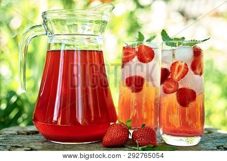 Fresh Strawberry Lemonade With Ice And Mint In Glasses And Jug On Wood Table With Green Background O