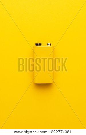 Blank Nine-volt Battery. Photo Of Nine-volt Battery On The Yellow Background. Yellow Nine-volt Batte