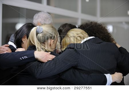 Team building event: businessmen in 'group hug' in office