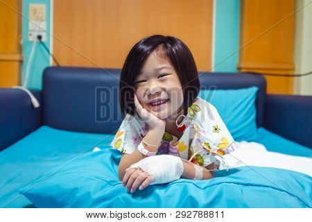 Illness Asian Child Smiling Happily And Looking At Camera. Girl Admitted In Hospital While Saline In