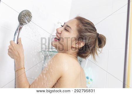 Woman Taking A Shower Enjoying Water Splashing On Her.