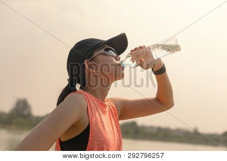 Beautiful Fitness Athlete Woman Drinking Water After Work Out Exercising On. Evening Summer.