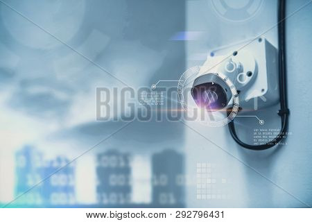 Cctv Security Camera On A Wall Blurred Cityscape Background.