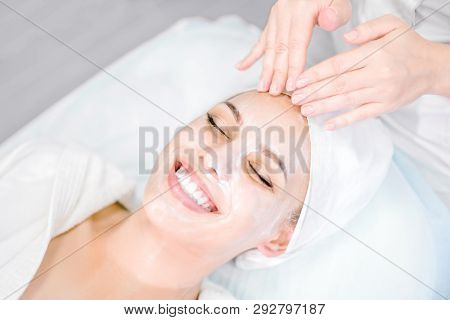 Beautician Makes Facial Massage With Mask. Beautiful Smiling Girl On Spa Procedure. Facial Care