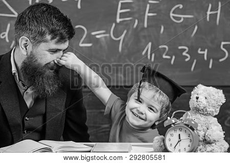 Playful child concept. Father with beard, teacher teaches son, little boy, while child pinching his nose. Teacher and pupil in mortarboard, chalkboard on background. Kid cheerful play with dad poster