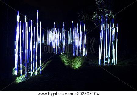 Light Tubes Illuminated Like Giant Glow Sticks At Night In Park During Holidays