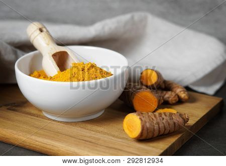 Turmeric Powder And Sliced Turmeric Roots Healthy Spice Asian Food Closeup Of A White Bowl With A Wo