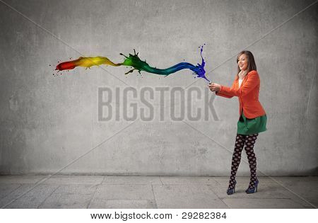 Beautiful woman squeezing a tube of paint