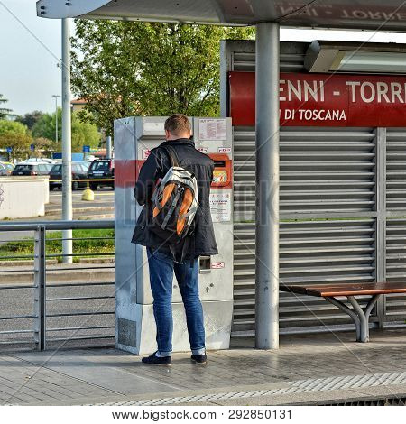 Italian Commute Trip. Man With A Backpack Buys A Ticket In A Ticket Machine At A Train Station. Publ