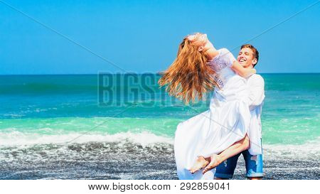 Happy Family On Honeymoon Holiday - Just Married Young Man And Woman Have Fun On Black Sand Beach. A