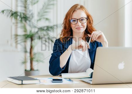 Positive Red Haired Young Female Entrepreneur Watches Business Webinar, Writes Email, Makes Notes In