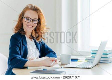 Self Confident Young Female Director Plans Work Process, Writes Main Theses In Notepad, Rewrites Inf