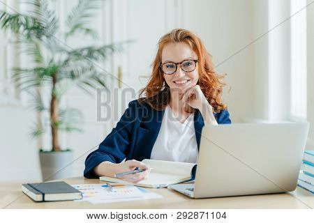 Photo Of Successful Ginger Female Freelancer Has Remote Work, Watches Webinar Online On Laptop Compu