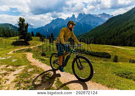 Single mountain bike rider on electric bike, e-mountainbike rides mountain trail. Man cycling on bike in Dolomites mountains. Cycling e-mtb enduro trail track. Outdoor sport activity.