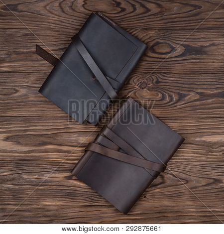 Black And Brown Handmade Leather Notebook Cover With Notebooks On Wooden Background. Stock Photo Of