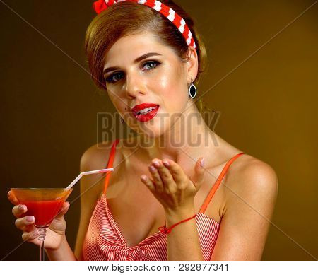 Pin up girl drink red long martini cocktails and flirtation and sends blow kiss on redux style themed night party.