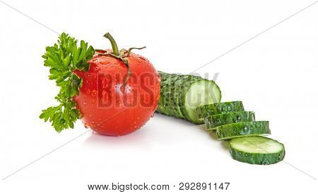 Isolated salad ingredients. Fresh vegetables (tomato and cucumber pieces) and parsley isolated on white background