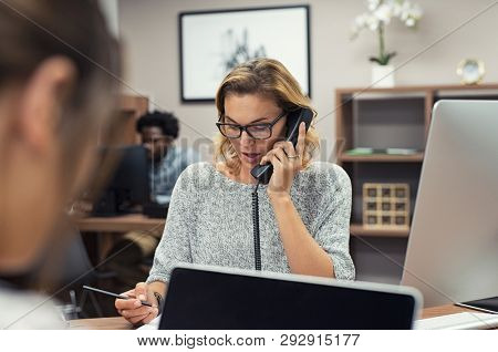 Mature businesswoman talking on phone in office. Casual business woman talking on landline phone in a creative agency. Beautiful blonde receptionist with eyeglasses taking client details over phone.