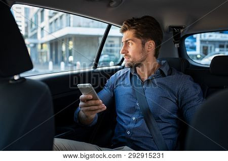 Stressed young businessman sitting in the back seat of car while thinking. Thoughtful business man holding phone sitting in car looking out of window with serious expression. Pensive man in taxi.