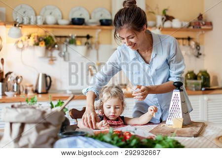 Family Are Cooking Italian Pizza In Cozy Home Kitchen. Happy Mother Is Teaching Cute Kid To Prepare