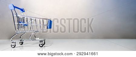 Miniature Blue Shopping Cart Or Shopping Trolley On The Table. Supermarket Grocery Push Cart. Banner