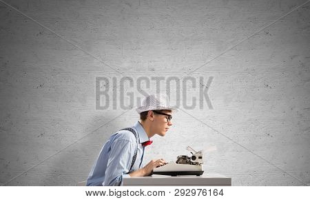 Young Man Writer In Hat And Eyeglasses Using Typing Machine While Sitting At The Table Against Gray