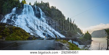 Summer Mountain Furebergsfossen Waterfall On Rocky Slope Near Road Along The Hardangerfjord Fiord, M