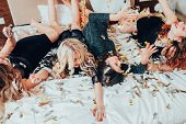 Theme party. Chill out. Group of girls in black relaxing on bed under confetti rain. BFF female gathering excitement. poster