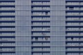 Building facade. modern hi-rise condominium clad with blue glass and Aluminum frame. curtain wall balcony and windows. not fully occupied luxury residential building. poster
