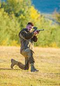 Man rifle for hunt. Mental preparation for hunting individual process. Hunter khaki clothes ready to hunt hold gun mountains background. Hunting shooting trophy. Hunter with rifle looking for animal poster