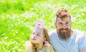 Family spend leisure outdoors, play girlish games. Child and father posing with crown and bow photo booth attributes. Dad and daughter sits on grass at grassplot, green background. Fatherhood concept poster