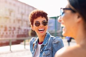 Happy women talking and laughing while walking in the city centre. Two beautiful girls having fun on the street. Portrait of young brazilian woman wearing sunglasses smiling at friend on the street.