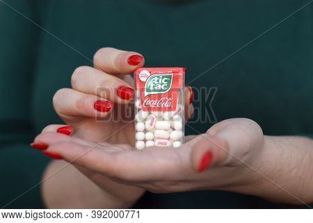 Young Girl Holds Tic-tac Hard Mints Pack With Coca-cola Taste. Tic Tac Is A Brand Of Small Hard Mint