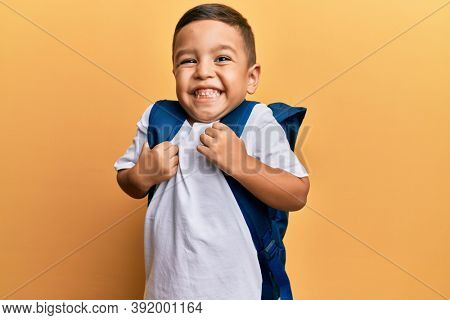 Adorable latin toddler smiling happy wearing student backpack over isolated yellow background.