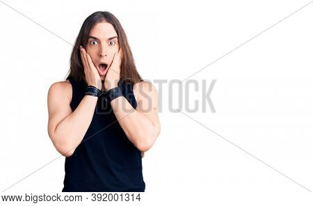 Young adult man with long hair wearing goth style with black clothes afraid and shocked, surprise and amazed expression with hands on face
