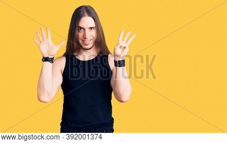 Young adult man with long hair wearing goth style with black clothes showing and pointing up with fingers number eight while smiling confident and happy.