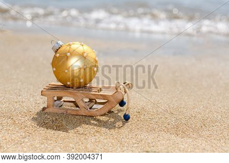 Christmas Sled With Golden Ball On The Tropical Beach Near Ocean, A Summer Christmas And Winter Holy