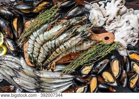 Raw Seafood Tiger Prawns, Shrimps, Blue Mussels, Octopuses, Sardines, Smelt. Black Wooden Background